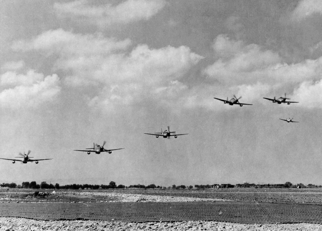 Red Tails of the 332nd Fighter Group take off to escort heavy bombers sent to bomb enemy oil fields at Blechhammer, Germany, on Aug. 7, 1944. Note the P-51s have wing tanks for the extra fuel needed for such long missions. (U.S. Air Force photo)