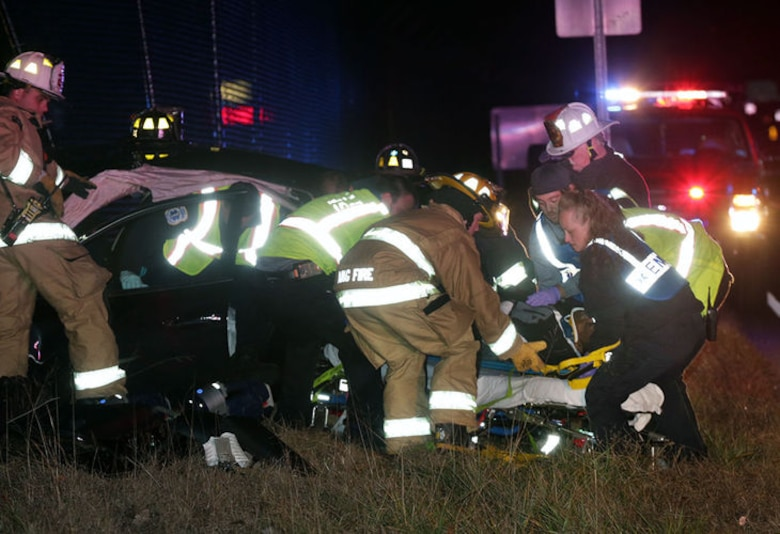 U.S. Air Force Airmen from the 177th Fighter Wing Fire Department as well as local first responders extract a car crash victim and place him on a stretcher on Dec. 4, 2014 in Egg Harbor Township, N.J. The vehicle was involved in a head-on collision, and crashed into the airport fence. (Courtesy photo, Michael Ein, Press of Atlantic City)