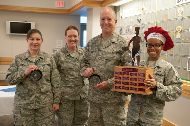 Staff Sgts. Sara Hardy and Todd Monroe, the Fourth Quarter Warrior Chef Competition's winning team, pose with their trophy skillets Dec. 4 at the Elkhorn Dining Facility. Both are from the 120th Force Support Squadron, Montana Air National Guard. Standing with them are Maj. Karen Dayle-Horsley, 341st Force Support Squadron commander, and event coordinator Staff Sgt. Amber Moore, 341st FSS noncommissioned officer in charge of missile alert feeding operations.  (U.S. Air Force photo/Tech. Sgt. Christina Perchine)
