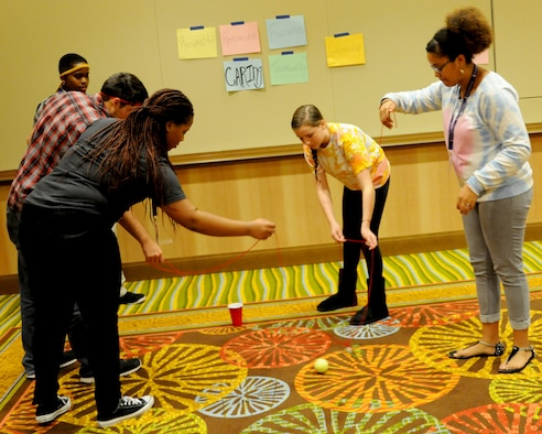 Teenagers work together as a team to try to navigate a ball into a cup using only yarn during an Air Force Reserve Yellow Ribbon Program event Nov. 21-23 in Orlando, Florida. Yellow Ribbon events help provide reservists and their loved ones access to the resources they need to help booster morale and welfare while maintaining resiliency during all stages of a deployment. (U.S. Air Force photo by Master Sgt. Shanda De Anda)