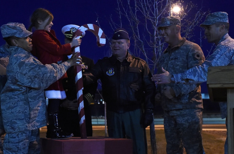 A 460th Space Wing 'panther cub' helps Team Buckley commanders and chiefs flip the switch to light the base tree during a tree-lighting ceremony Dec. 9, 2014, at the 460th SW headquarters building on Buckley Air Force Base, Colo. The annual tree lighting concluded with a visit from the 460th SW mascot, Buck Lee, dressed as Santa Claus, as well as hot chocolate and cookies. (U.S. Air Force photo by Airman 1st Class Samantha Saulsbury/Released)