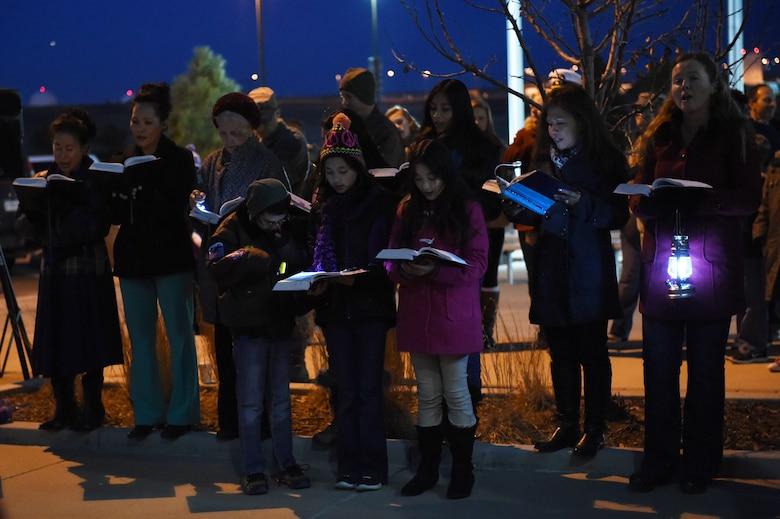 Members of the Buckley Chapel Catholic Choir Group sing Christmas songs during a tree-lighting ceremony Dec. 9, 2014, at the 460th Space Wing headquarters building on Buckley Air Force Base, Colo. The annual tree lighting concluded with a visit from the 460th SW mascot, Buck Lee, dressed as Santa Claus, as well as hot chocolate and cookies. (U.S. Air Force photo by Airman 1st Class Samantha Saulsbury/Released)
