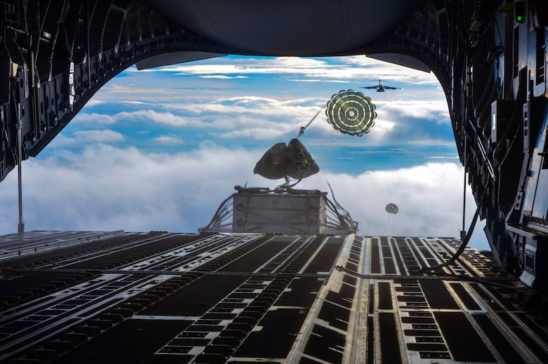 Two heavy container delivery systems plunge from the back of a C-17 Globemaster III aircraft to forces on the ground during the simulated Rainier War Dec. 6, 2014, over the Rainier drop zone, Wash. The Joint Concept for Entry Operations doctrine defines forcible entry as the seizing and holding of a lodgment in the face of armed opposition. (U.S. Air Force photo/Staff Sgt. Russ Jackson)