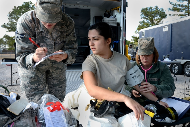 U.S. Air Force Senior Airman Chantal Hogue, 20th Civil Engineer Squadron emergency management apprentice, has her vital signs taken by 20th Aerospace Medicine Squadron medical technicians during an integrated base emergency response capability training exercise at Shaw Air Force Base, S.C., Dec. 9, 2014. Before suiting up in contamination gear, each of the three Airmen who were a part of the initial entry team had their vital signs taken before and after walking through the contaminated area. (U.S. Air Force photo by Airman 1st Class Jensen Stidham/Released)