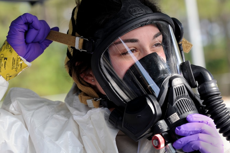 U.S. Air Force Senior Airman Chantal Hogue, 20th Civil Engineer Squadron emergency management apprentice, adjusts her mask during an integrated base emergency response capability training at Shaw Air Force Base, S.C., Dec. 9, 2014. During the exercise, Hogue and two other Airmen acted as the initial entry team in response to a simulated chemical attack. (U.S. Air Force photo by Airman 1st Class Michael Cossaboom/Released)