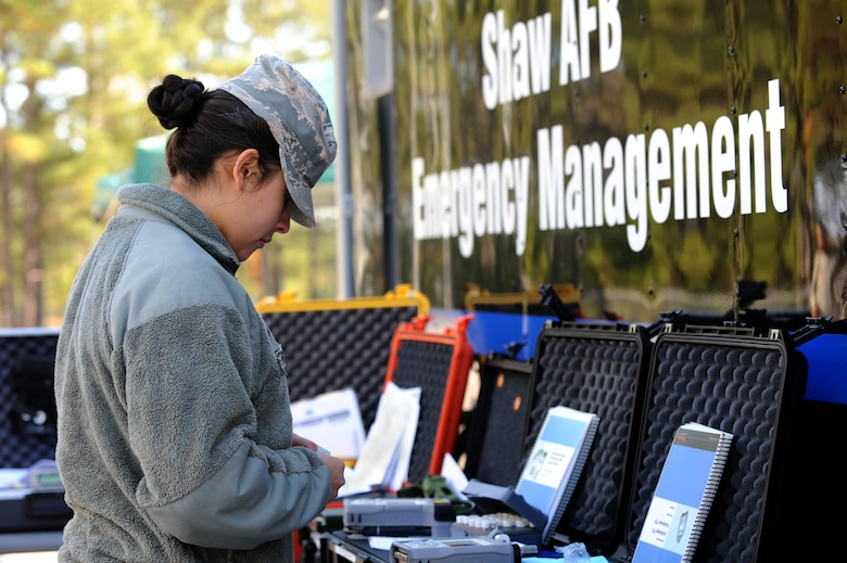 U.S. Air Force Airman 1st Class Cynthia Romero, 20th Civil Engineer Squadron emergency management apprentice, examines her gear during an integrated base emergency response capability training at Shaw Air Force Base, S.C., Dec. 9, 2014. The 20th CES emergency management flight and the 20th Aerospace Medicine Squadron bioenviromental flight were tested on their abilities to react and work together in the event of a chemical attack were to happen on base. (U.S. Air Force photo by Airman 1st Class Michael Cossaboom/Released)