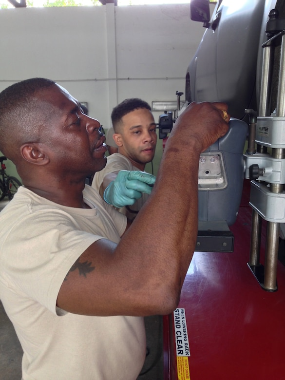 D.C. National Guard soldiers Master Sgt. Jesse Evans (left) and Sgt. Girard King (right) fix a Jamaica Defence Force truck on the second day of a weeklong subject matter expert exchange. Expert vehicle mechanic soldiers and airmen from the D.C. National Guard are here to share best practices with their JDF counterparts National Guard Bureau's State Partnership Program. Evans is a D surface maintenance inspector supervisor and King is a vehicle mechanic. (U.S. Air National Guard photo by Capt. Renee Lee)