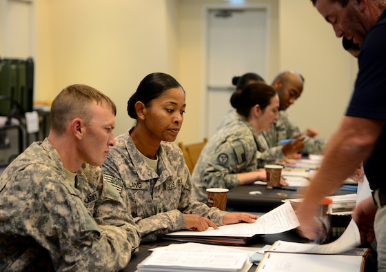 U.S. Army Sgt. Sheena Lang, center, Area Support Group-Qatar finance, helps participants of a Noncombatant Evacuation Operations exercise fill out paperwork, Dec. 6, 2014, at Camp As Sayliyah, Qatar. The exercise allowed noncombatants and military members from the Air Force and Army to rehearse evacuation procedures in the event of an emergency in the host nation. (U.S. Air Force photo by Senior Airman Kia Atkins)