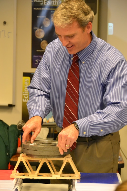 WINCHESTER, Va. - Engineer Bob Thomas adds weights to the bridge that students built to demonstrate load.