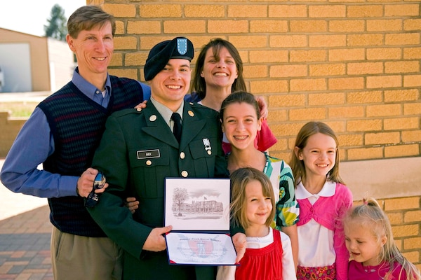 Private 1st Class Scott Wayne proudly holds his newly earned high school diploma while posing for photos with his family members at the Patriot Academy's first graduation ceremony at the Muscatatuck Urban Training Center in Butlerville, Ind., March 18, 2010. The Army National Guard's Patriot Academy is the U.S. military's first accredited high school.