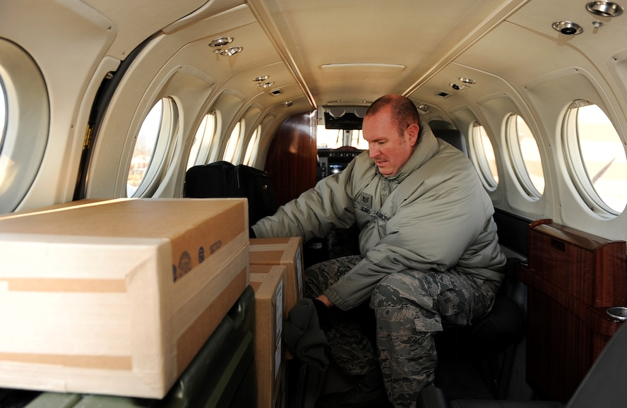 U.S. Air Force Tech. Sgt. John King, a Defense Courier Station Offutt courier and station superintendent, sorts through the classified parcels filling the fuselage of a C-12 aircraft on Offutt Air Force Base, Neb., Nov. 18, 2014. The Defense Courier Station Offutt averages more than 100 missions and 95,000 miles per year via airlift and road system. (U.S. Air Force photo by Josh Plueger/Released)