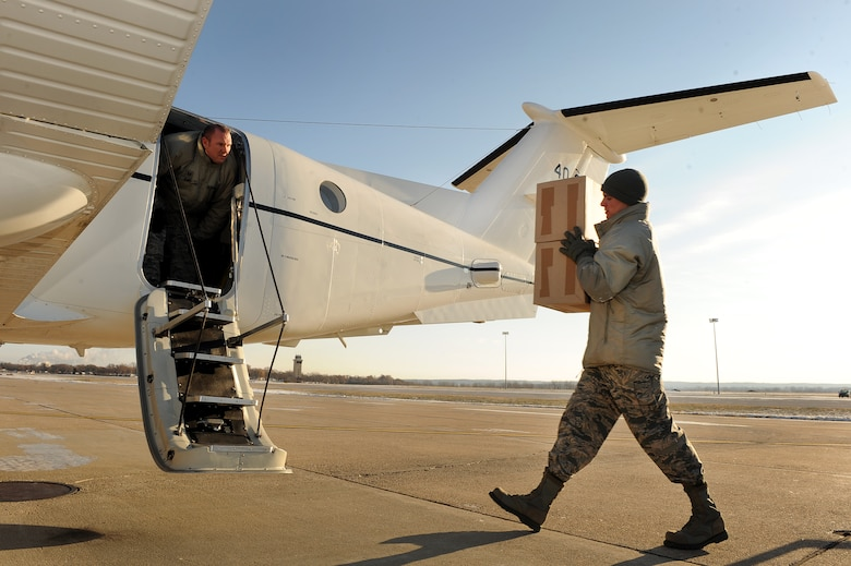U.S. Air Force Staff Sgt. Jonathan Clay, a Defense Courier Station Offutt courier, hands classified packages to fellow courier, U.S. Air Force Tech Sgt. John King, on the flightline at Offutt Air Force Base, Neb., Nov. 18, 2014. The Defense Courier Station Offutt is tasked with servicing nine states and 130 customers, comprising the second largest geographical area of responsibility for all of the 18 worldwide defense courier units. (U.S. Air Force photo by Josh Plueger/Released)