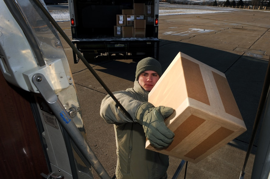 U.S. Air Force Staff Sgt. Jonathan Clay, a Defense Courier Station Offutt courier, transfers packages from a box truck to the fuselage of a C-12 aircraft at Offutt Air Force Base, Neb., Nov. 18, 2014. Clay along with another courier will hand deliver the packages at numerous points across the Midwest all within one duty day.  (U.S. Air Force photo by Josh Plueger/Released)