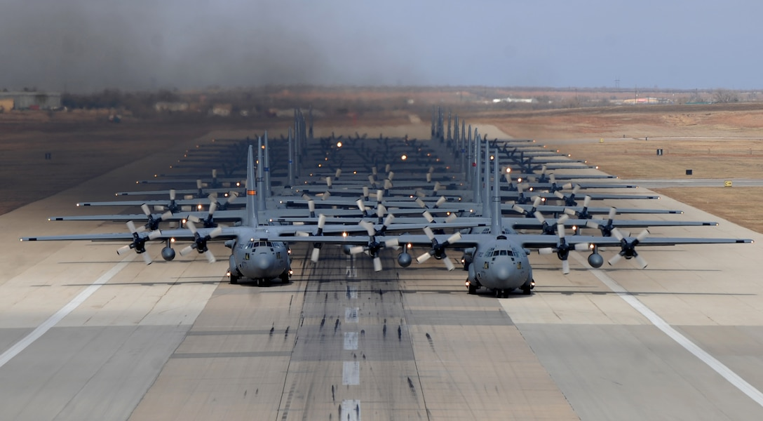 Eleven C-130H Hercules' from various Air National Guard units and thirteen C-130J Super Hercules' from the 317th Airlift Group at Dyess Air Force Base, Texas, prepare to take off from Dyess AFB in support of the U.S. Air Force Weapons School's Joint Forcible Entry Exercise 14B Dec. 6, 2014. In addition to the C-130s, the JFEX included approximately 20 C-17 Globemaster IIIs and various other aircraft. (U.S. Air Force photo by Airman 1st Class Alexander Guerrero/Released)
