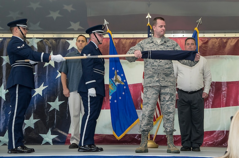 Brig. Gen. Carl Buhler, Ogden Air Logistics Complex commander, unfurls the 575th Aircraft Maintenance Squadron guidon as part of the 575th AMXS activation ceremony Dec. 11 at Joint Base San Antonio-Randolph. The 575th AMXS is a geographically separate unit assigned to the 309th Aircraft Maintenance Group, Ogden Air Logistics Complex Hill Air Force Base, Utah. The squadron is responsible for depot level maintenance, restoration and modification of over 500 T-38 Talon aircraft for the United States Air Force and Navy. (U.S. Air Force photo by Johnny Saldivar)