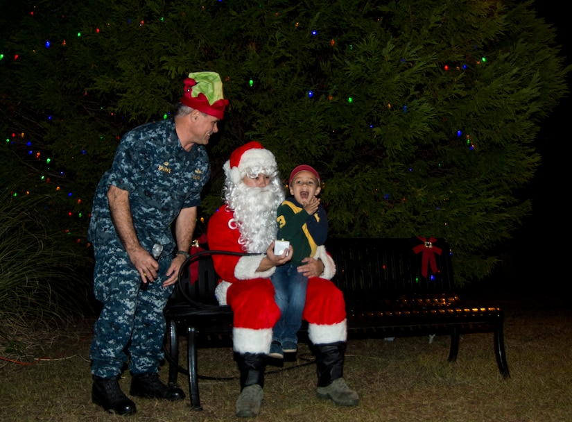 U.S. Navy Capt. Timothy Sparks, Joint Base Charleston deputy commander,   along with Santa Claus and a young volunteer light the Christmas tree during the annual Christmas tree lighting ceremony Dec. 4, 2014, on JB Charleston - Weapons Station, S.C. The tree lighting is an annual tradition held at both the Air Base and Weapons Station to kick off the holiday season. (U.S. Air Force photo/Senior Airman Melissa Goslin)