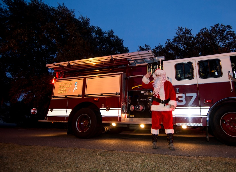 Santa makes a surprise entrance on a fire truck during the annual Christmas tree lighting ceremony Dec. 4, 2014, on Joint Base Charleston - Weapons Station, S.C. The tree lighting is an annual tradition held at both the Air Base and Weapons Station to kick off the holiday season. (U.S. Air Force photo/Senior Airman Melissa Goslin)
