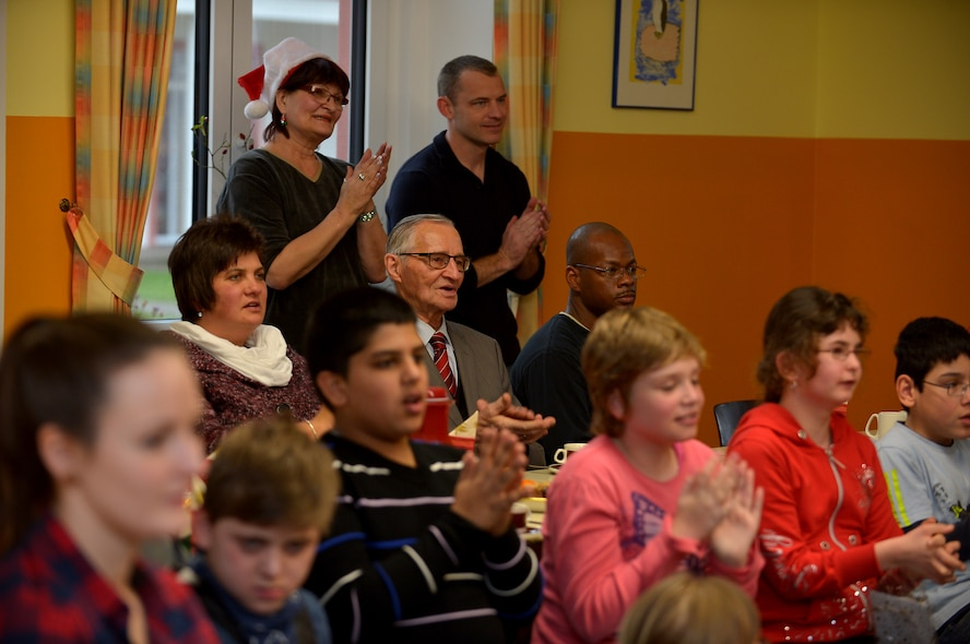 U.S. Air Force Airmen and civilians from Spangdahlem Air Base, Germany, sing carols with children from St. Martin School in Bitburg, Germany, Dec. 8, 2014. Gifts were presented to the children by the 52nd Civil Engineer Squadron leadership, who raise funds each year to support the school. (U.S. Air Force photo by Airman 1st Class Kyle Gese/Released)