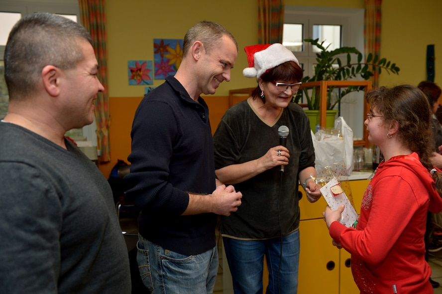 U.S. Air Force Master Sgt. Thomas McGrew, left, U.S. Air Force Lt. Col. Christopher Meeker, middle, and Gertie Appleby, right, all from the 52nd Civil Engineer Squadron, help Sankt Nikolaus pass out gifts to St. Martin School children in Bitburg, Germany, Dec. 8, 2014. Spangdahlem Airmen raised more than $10,000 and 2,000 volunteer hours to support St. Martin Schools' special needs children in 2014. (U.S. Air Force photo by Airman 1st Class Kyle Gese/Released)