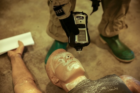 A Chemical, Biological, Radiological and Nuclear defense specialist survey's the readings from an unknown substance on a simulated casualty during an assessment/consequences management exercise Dec. 5 at Camp Hansen. The Marines are with the 31st Marine Expeditionary Unit.