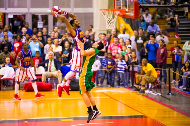 Harlem Globetrotters forward, Tydran 'Crash' Beaty, throws down the fanatic game winning dunk over a Washington Generals defender Dec. 9 at The Foster Field House on Camp Foster. The Harlem Globetrotters displayed their basketball artistry to service members and their families. The athletic basketball display was an opportunity for the Harlem Globetrotters to give a little taste of home to the service members serving overseas. The event was a part of the Harlem Globetrotters 13th military tour, in which the team travels overseas to U.S. military installations throughout Japan. The game was presented by Navy Entertainment, Leatherneck Tour and Marine Corps Community Services.