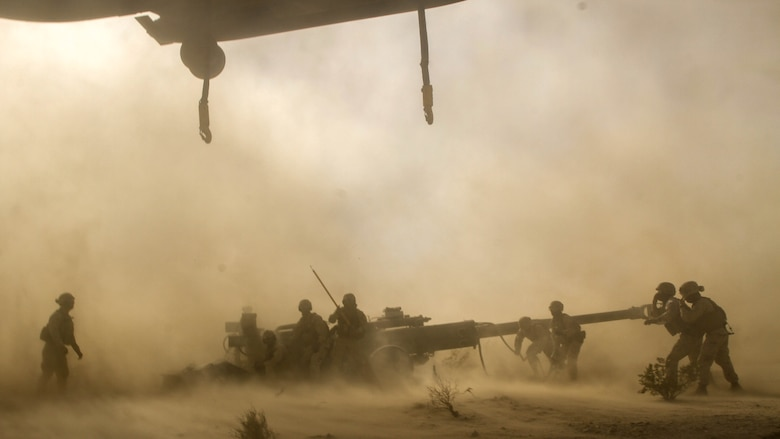 Marines with Landing Support Platoon, Truck Support Company, Combat Logistics Battalion 5, prepare to attach an M777 Howitzer to a CH-53E Super Stallion as it hovered over the gun during Exercise Steel Knight 2015 at Marine Corps Air Ground Combat Center Twentynine Palms, Calif., Dec. 9, 2014. The exercise gave the Marines the opportunity to refine and rehearse essential skills needed in a combat environment. Steel Knight is an annual exercise that includes elements from the entire I Marine Expeditionary Force. The exercise focuses on conventional operation and provides realistic training that prepares Marine for overseas operations. (U.S. Marine Corps photo by Cpl. Christopher J. Moore/Released)