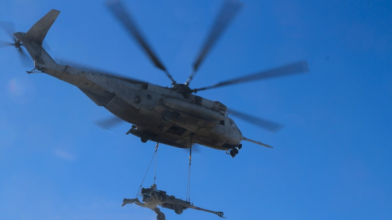 A CH-53E Super Stallion carries an M777 Howitzer that Marines with Landing Support Platoon, Truck Support Company, Combat Logistics Battalion 5, attached to the helicopter as it hovered above them during Exercise Steel Knight 2015 at Marine Corps Air Ground Combat Center Twenty-nine Palms, Calif., Dec. 9, 2014. The exercise gave the Marines the opportunity to refine and rehearse essential skills needed in a combat environment. Steel Knight is an annual exercise that includes elements from the entire I Marine Expeditionary Force. The exercise focuses on conventional operations and provides realistic training that prepares Marine for overseas operations. (U.S. Marine Corps photo by Cpl. Christopher J. Moore/Released)