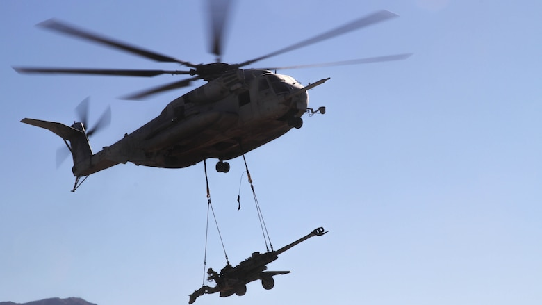 A CH-53E Super Stallion carries an M777 Howitzer that Marines with Landing Support Platoon, Truck Support Company, Combat Logistics Battalion 5, attached to the helicopter as it hovered above them during Exercise Steel Knight 2015 at Marine Corps Air Ground Combat Center Twenty-nine Palms, Calif., Dec. 9, 2014. The exercise gave the Marines the opportunity to refine and rehearse essential skills needed in a combat environment. Steel Knight is an annual exercise that includes elements from the entire I Marine Expeditionary Force. The exercise focuses on conventional operation and provides realistic training that prepares Marine for overseas operations. (U.S. Marine Corps photo by Cpl. Christopher J. Moore/Released)