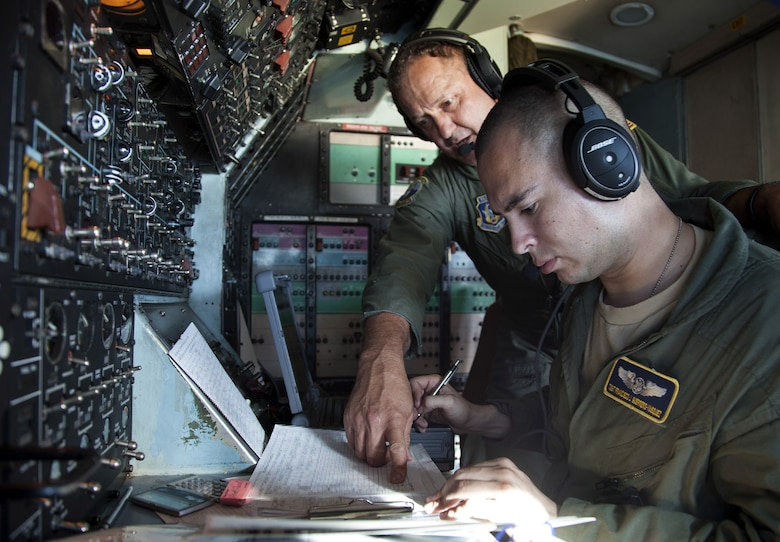 Senior Master Sgt. Timothy Nichols, left, discusses fuel consumption with Tech. Sgt. Francisco Guerrero-Vasquez on the flight deck of a C-5B Galaxy on a Pacific channel mission. Both Air Force Reserve aviators are assigned to the 312th Airlift Squadron, Travis Air Force Base, Calif. Nichols is a flight engineer evaluator and Guerrero-Vasquez is a flight engineer. (U.S. Air Force photo/Lt. Col. Robert Couse-Baker)