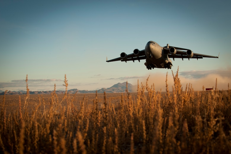 A C-17 Globemaster III takes off from a degraded airfield Dec. 6, 2014, during the U.S. Air Force Weapons School's Joint Forcible Entry Exercise 14B at the Nevada Test and Training Range. JFEX exercises participants' ability to synchronize aircraft movements from geographically separated bases, command large formations of dissimilar aircraft in high-threat airspace, and tactically deliver and recover combat forces via air drops and combat landings on an unimproved landing strip. The C-17 is assigned to March Air Reserve Base, Calif. (U.S. Air Force photo/Airman First Class Joshua Kleinholz)