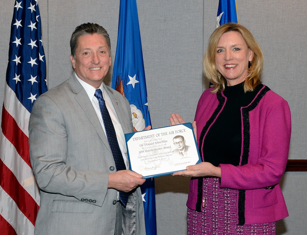 Secretary of the Air Force Deborah Lee James presents the 2014 Harold Brown Award to Dr. Don Erbschloe, Air Mobility Command's chief scientist, Dec. 9, 2014, during a ceremony held in the Pentagon, Washington, D.C. The award is given by the Air Force to a scientist or engineer who applies scientific research to solve a problem critical to the needs of the Air Force. (U.S. Air Force photo/Andy Morataya)