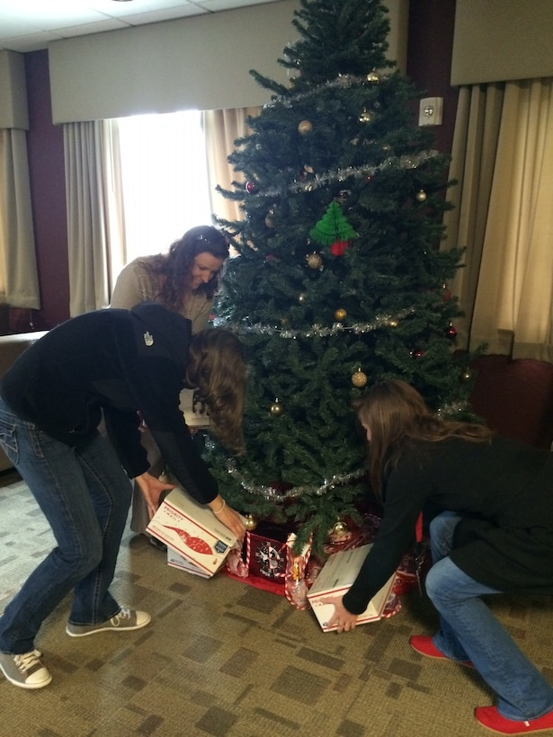 Icy Munchel, left, Megan Goold, center, and Katie Contento place care packages under a Christmas tree at Marine Corps Air Station Cherry Point, N.C., Dec. 3, 2014. Members of the In-Service Support Center with the Fleet Readiness Center East at Cherry Point donated more than 118 care packages to Marines and Sailors with Marine Aerial Refueler Transport Squadron 252. The packages contained toiletries, comfort items and video games. Munchel is the family readiness officer with VMGR-252; Goold is a chemist with Naval Air Systems Command; and Conento is a T-64 engineer with NAVAIR.
