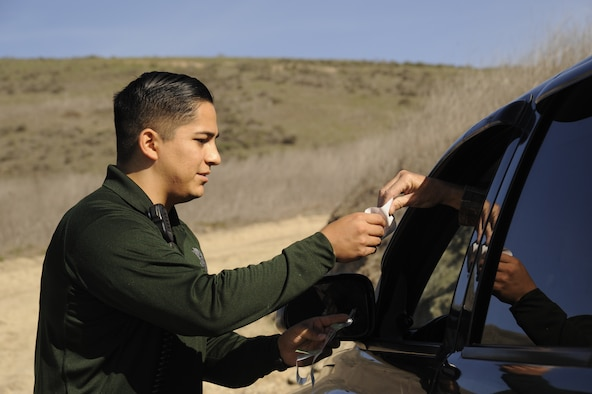 Staff Sgt. Michael Vera checks a hunter's credentials, Dec. 9, 2014, at Vandenberg Air Force Base, Calif. The 10-man team of conservation officers covers the area on four-wheeled vehicles and horses, ensuring security and safety for the base's human and animal residents. Vera is a 30th Security Forces Squadron conservation officer. (U.S. Air Force photo/Airman 1st Class Ian Dudley)
