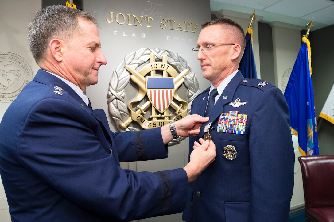 Lt. Gen. David L. Goldfein pins the Airman's Medal on Col. Richard Poston Dec. 10, 2014, in a ceremony held at the Pentagon in Washington D.C. Poston was recognized for his heroic actions on July 6, 2013, when he saved a young female from drowning in the Potomac River. Goldfein is the director of the Joint Staff and Poston is the assistant deputy director for political military affairs, strategic plans and policy, J-5 DD-Africa. (Defense Department photo/ U.S. Army Staff Sgt. Sean K. Harp)