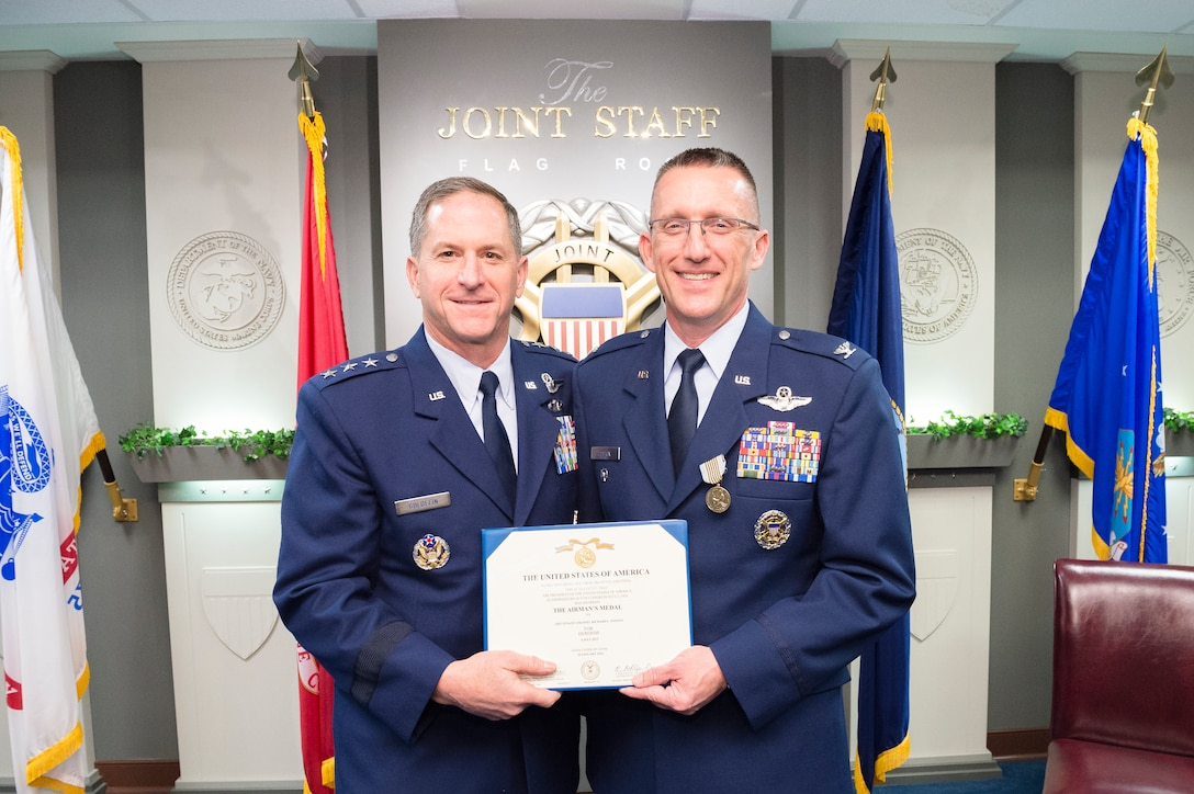 Lt. Gen. David L. Goldfein and Col. Richard Poston pose for a photo Dec. 10, 2014, during Poston's Airman's Medal ceremony held at the Pentagon in Washington D.C. Poston was recognized for his heroic actions on July 6, 2013, when he saved a young female from drowning in the Potomac River. Goldfein is the director of the Joint Staff and Poston is the assistant deputy director for political military affairs, strategic plans and policy, J-5 DD-Africa. (Defense Department photo/ U.S. Army Staff Sgt. Sean K. Harp)