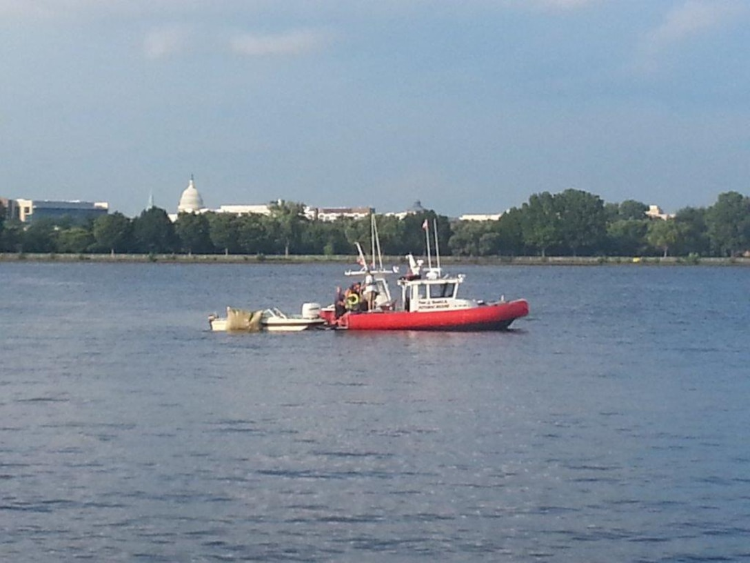 A boat pulls out submerged vessel from the Potomac River in Washington D.C. This photo was captured a couple days after Col. Richard Poston helped save a young girl from drowning. She, along with the other four members, was aboard the vessel when it went under. (Courtesy photo/U.S. Air Force Col. Richard Poston)