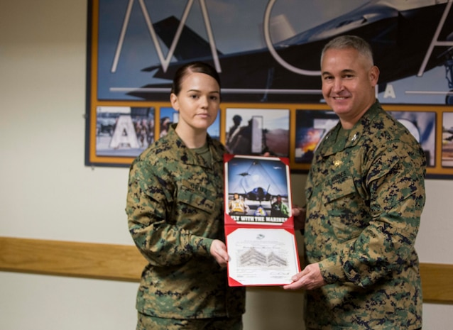 Sgt. Erika M. Cruz, the non-commissioned officer-in-charge at the military post office on Marine Corps Air Station Yuma, Ariz., receives her promotion warrant after she was meritoriously promoted by Col. Ricardo Martinez, the station commanding officer, following her selection as Marine of the Year for Marine Corps Installations West, Monday, Nov. 3, 2014.