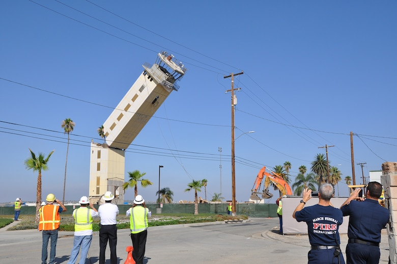 Team March members look on as contractors expertly topple the 56-year-old air traffic control tower at March Air Reserve Base, Calif.. Replaced by a new, seismically-engineered tower, the old tower hit the ground at 9:20 a.m., Aug. 19, 2014. (U.S. Air Force photo/Linda Welz)