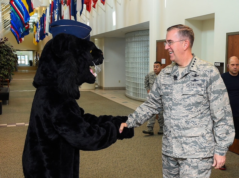 Buck Lee, 460th Space Wing mascot, left, shakes hands with General John E. Hyten, Commander of Air Force Space Command, Dec. 10, 2014, in the fitness center on Buckley Air Force Base, Colo. During General Hyten's first visit to Buckley after assuming AFSPC command Aug 2014, he received a mission brief, toured the 460th Operations Group Mission Control Station and spoke with Airmen at a commander's call. AFSPC provides space and cyberspace capabilities for the joint force and the nation, and the 460th SW is one of several units in Colorado and around the world that supports AFSPC's mission. (U.S. Air Force photo by Senior Airman Riley Johnson/Released)