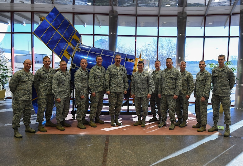 General John E. Hyten, Commander of Air Force Space Command, center left, poses for a group photo with 460th Space Wing Airmen Dec. 10, 2014, in the 460th Operations Group Mission Control Station on Buckley Air Force Base, Colo. During General Hyten's first visit to Buckley after assuming AFSPC command Aug 2014, he received a mission brief, toured the mission control station and spoke with Airmen at a commander's call. AFSPC provides space and cyberspace capabilities for the joint force and the nation, and the 460th SW is one of several units in Colorado and around the world that supports AFSPC's mission. (U.S. Air Force photo by Senior Airman Riley Johnson/Released)