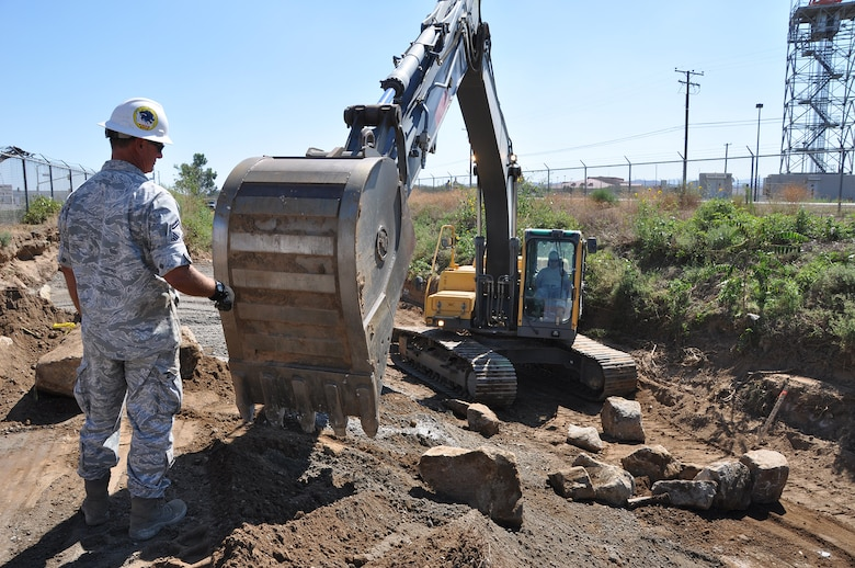 Senior Master Sgt. Robert Montgomery, heavy equipment superintendent, 163rd Civil Engineer Squadron, California Air National Guard, March Air Reserve Base, operates an excavator to move large rocks on the Heacock Channel project, Sept. 11, 2014. Reservists and Guardsmen from March participated in a joint-construction project to repair the erosion damage and sediment accumulation to the Heacock Channel on the east side of base. (U.S. Air Force photo/Senior Airman Russell S. McMillan)