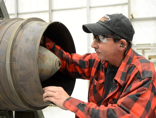 James Skipper, C-130 Engine Shop mechanic, shows a rear bearing support crack on a C-130 engine. (U.S. Air Force photo by Ed Aspera)