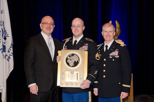 Lt. Col. Brian Beckno, an Army instructor at Air University's Air Command and Staff College, Maxwell Air Force Base, Alabama, accepts the 2014 Secretary of Defense Award for Excellence in Maintenance Training, Advice and Assistance of Foreign Security Forces (Ministerial Category) on behalf of the men and women he led as commander of 2nd Battalion, 87th Infantry Regiment, or Task Force Catamount.  Task Force Catamount earned the award for their work with the Afghan National Army's 4th Brigade, 203rd Corps last year.  (Air Force Photo by Master Sgt. David Maxwell, 117th Air Refueling Wing/Cleared)