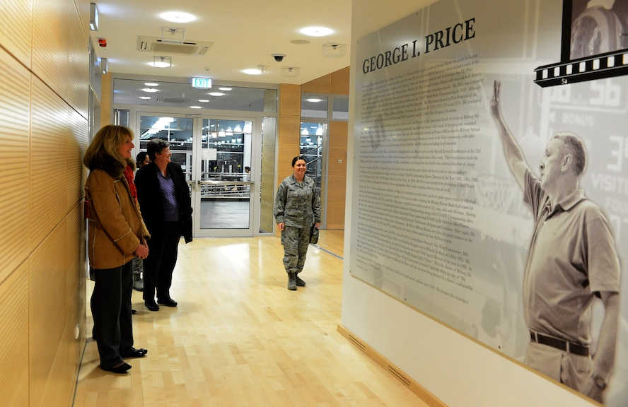 Cheryl Roberson, left, wife of U.S. Air Force Lt. Gen. Darryl Roberson, 3rd Air Force and 17th Expeditionary Air Force commander, reads the tribute to George Price in the George Price Gymnasium on Spangdahlem Air Base, Germany, Dec. 9, 2014. Roberson also attended the commander's all call where her husband spoke on key Air Force issues. (U.S. Air Force photo by Airman 1st Class Luke Kitterman/Released)