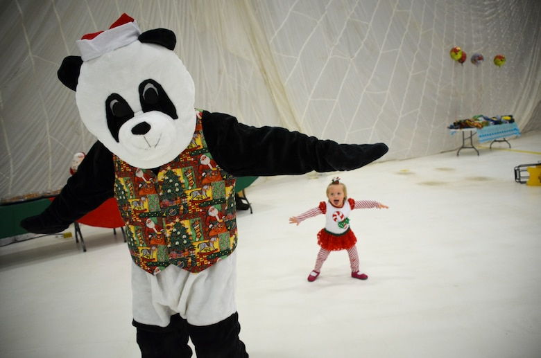Katherine Mosses, 3, dances with a panda bear as she waits to see Santa Claus.  The annual Flight to the North Pole is hosted by the 128th Air Refueling Wing, Wisconsin Air National Guard, Milwaukee Dec. 13, 2014 here.  (U.S. Air National Guard photo by Master Sgt. Thomas J. Sobczyk/Released)