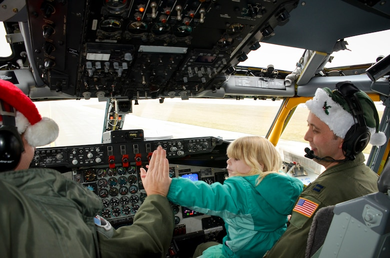 Olivia Wagner, 3, high-fives Major Keyes as she helps pilot the KC-135 Stratotanker to the North Pole.  The annual Flight to the North Pole is hosted by the 128th Air Refueling Wing, Wisconsin Air National Guard, Milwaukee Dec. 13, 2014 here.  (U.S. Air National Guard photo by Master Sgt. Thomas J. Sobczyk/Released)