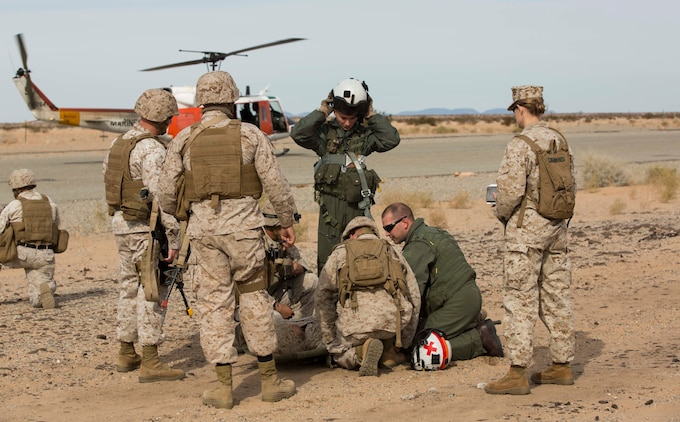 Marines with Marine Wing Support Squadron 371 and a team from Search and Rescue with Headquarters and Headquarters Squadron pick up a casualty during the security force exercise in support of pre-deployment training Dec. 7-10, 2014, at the Auxiliary Landing Field II on Marine Corps Air Station Yuma, Ariz. Casualty evacuations were a realistic scenario that Marines learned to work through and respond as they conducted perimeter patrols. (U.S. Marine Corps photo by Cpl. Reba James/ Released)