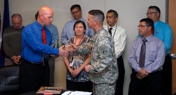 Lt. Col. Charles Gray, Deputy Commander, New England District, presents Stephen Dunbar and other members of the Elizabeth Mine Superfund Site Project Delivery Team (PDT) the prestigious Green Dream Team Award in the 2014 USACE Sustainability Award Program during a virtual awards ceremony held via video teleconference (VTC) on Oct. 7, 2014.