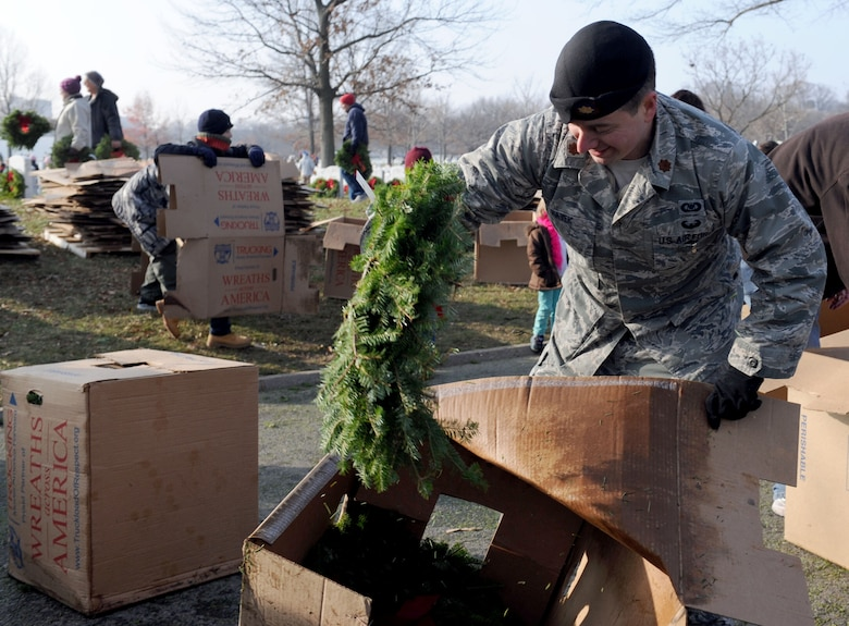 Maj. Michael Hayek unpacks wreaths from a box during the 23rd Annual National Wreaths Across America Day Dec. 13, 2014, at Arlington National Cemetery, Virginia. Hayek, the close air support branch chief and the air liaison officer career field manager at the Pentagon, was one of the nearly 50,000 volunteers at Arlington. (U.S. Air Force photo/Staff Sgt. Christopher Gross)