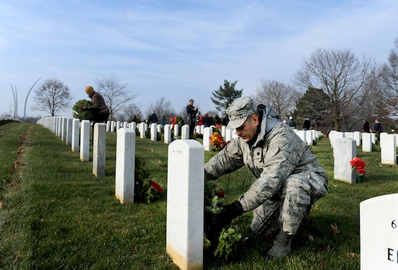 Lt. Col. David Burnett lays a wreath on a tombstone during the 23rd Annual National Wreaths Across America Day Dec. 13, 2014, at Arlington National Cemetery, Virginia. Burnett, assigned to the Joint Staff, J1, Plans and Readiness Personnel Readiness Division at the Pentagon, was one of the nearly 50,000 volunteers at Arlington. (U.S. Air Force photo/Staff Sgt. Christopher Gross)